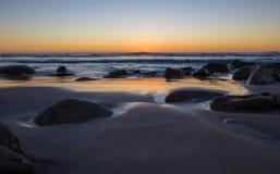 Puesta del sol de oro hermosa sobre Rocky Beach foto de archivo
