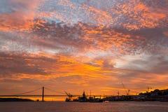 Puesta del sol de oro increíble sobre el río el Tajo, puente 25 de abril y el puerto de Lisboa, Portugal Fotos de archivo