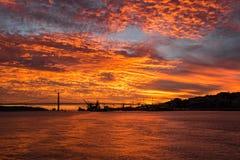 Puesta del sol de oro increíble sobre el río el Tajo, puente 25 de abril y el puerto de Lisboa, Portugal Foto de archivo