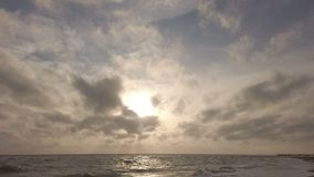 Puesta del sol de oro de la hora que sorprende en el mar con el cielo dramático y la luz hermosa entre las nubes de cirro almacen de video