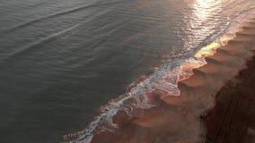 Puesta del sol de oro de la visión aérea sobre el mar con las ondas que se estrellan en la orilla con reflexiones hermosas en e metrajes