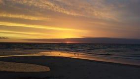 Puesta del sol de oro ligera en la playa Fotografía de archivo