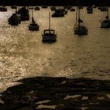 Puesta del sol de oro, reflexiones en el agua en la bahía tranquila, silueta de los barcos de navegación Imagen de archivo