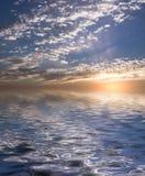 Puesta del sol de oro sobre el agua fotos de archivo libres de regalías