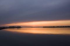 Puesta del sol de oro sobre el agua fotografía de archivo libre de regalías