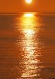 Puesta del sol de oro sobre el agua Fotos de archivo
