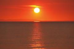 Puesta del sol de oro sobre el agua Imagenes de archivo