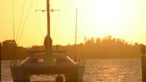 Puesta del sol de oro sobre el agua con un velero en primero plano metrajes