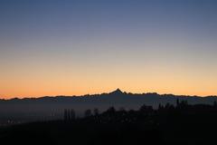 Puesta del sol de oro sobre el horizonte de la colina y de las montañas Foto de archivo
