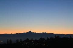 Puesta del sol de oro sobre el horizonte de la colina y de las montañas Foto de archivo libre de regalías