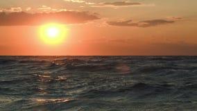 Puesta del sol de oro sobre el mar agitado