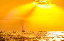 Puesta del sol de oro sobre el mar con la silueta del barco Foto de archivo