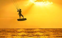 Puesta del sol de oro sobre el mar con los hombres kiting la silueta Fotos de archivo libres de regalías