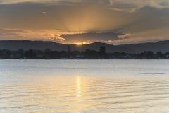 Puesta del sol de oro suave sobre la bahía con la alta nube imagenes de archivo