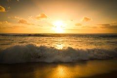 Puesta del sol de oro y una onda que se estrella Imágenes de archivo libres de regalías