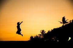 Puesta del sol de salto de la playa de Sanur de la silueta de la muchacha de Bali Fotografía de archivo