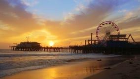 Puesta del sol de Santa Monica California en la rueda de Pier Ferris y reflexión en la playa almacen de video