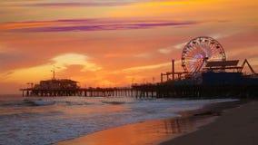 Puesta del sol de Santa Monica California en la rueda de Pier Ferris y reflexión en la playa almacen de metraje de vídeo