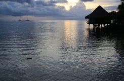 Puesta del sol de Tahitian con la casa de planta baja Foto de archivo libre de regalías