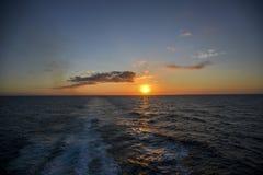 Puesta del sol de un barco de cruceros de salida Imagenes de archivo