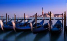 Puesta del sol de Venecia con las góndolas borrosas Cielo azul y púrpura asombroso Imagenes de archivo