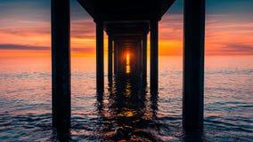 Puesta del sol debajo de Brighton Jetty Imagen de archivo libre de regalías