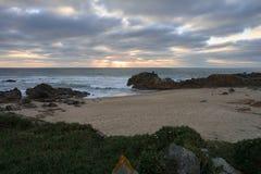 Puesta del sol debajo de las nubes oscuras en una playa rocosa foto de archivo libre de regalías