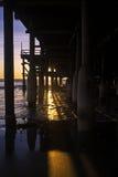 Puesta del sol debajo de un embarcadero Imagen de archivo libre de regalías