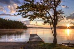 Puesta del sol del Adirondacks del árbol y del muelle Imagen de archivo