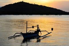 Puesta del sol del Balinese del con un barco de pesca anclado Imagen de archivo libre de regalías