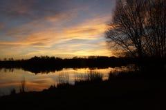 Puesta del sol del invierno en un lago en Francia Imagen de archivo