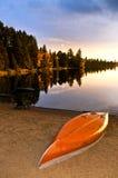 Puesta del sol del lago con la canoa en la playa foto de archivo