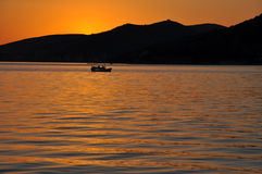 Puesta del sol del mar con la silueta del barco Imágenes de archivo libres de regalías