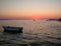 Puesta del sol del mar con los muelles y los barcos Imagen de archivo libre de regalías
