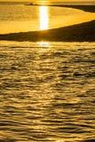 Puesta del sol del oro sobre el escupitajo de la arena Fotos de archivo libres de regalías