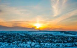 Puesta del sol del paisaje del invierno sobre el pueblo Foto de archivo libre de regalías