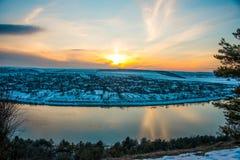 Puesta del sol a del paisaje del invierno sobre el pueblo Fotografía de archivo