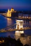 Puesta del sol del paisaje urbano de Budapest con el puente de cadena en frente sobre Danubio Foto de archivo libre de regalías