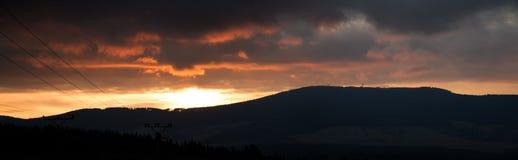 Puesta del sol del panorama sobre las montañas al cielo cubierto Imagenes de archivo