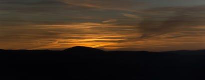 Puesta del sol del panorama sobre las montañas al cielo cubierto Fotos de archivo