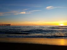 Puesta del sol del rosa del amarillo anaranjado en el embarcadero 4k de la playa Foto de archivo libre de regalías