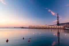Puesta del sol delante de la ciudad de Trieste Foto de archivo