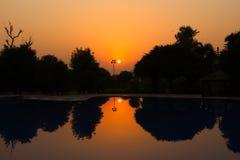 Puesta del sol delante del lago imagenes de archivo