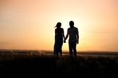 Puesta del sol delantera que camina de los pares jovenes Foto de la puesta del sol Imagen de archivo libre de regalías