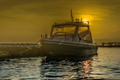 + puesta del sol detrás del barco + Imágenes de archivo libres de regalías