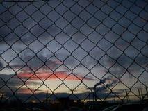 Puesta del sol detrás de la cerca imágenes de archivo libres de regalías