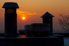 Puesta del sol detrás de la chimenea Foto de archivo
