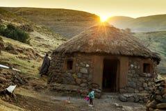 Puesta del sol detrás de la choza de Lesotho Imagenes de archivo