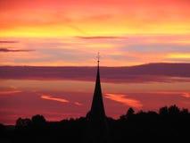 Puesta del sol detrás de la torre de iglesia Fotografía de archivo libre de regalías