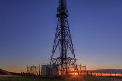 Puesta del sol detrás de la torre de las telecomunicaciones Fotos de archivo